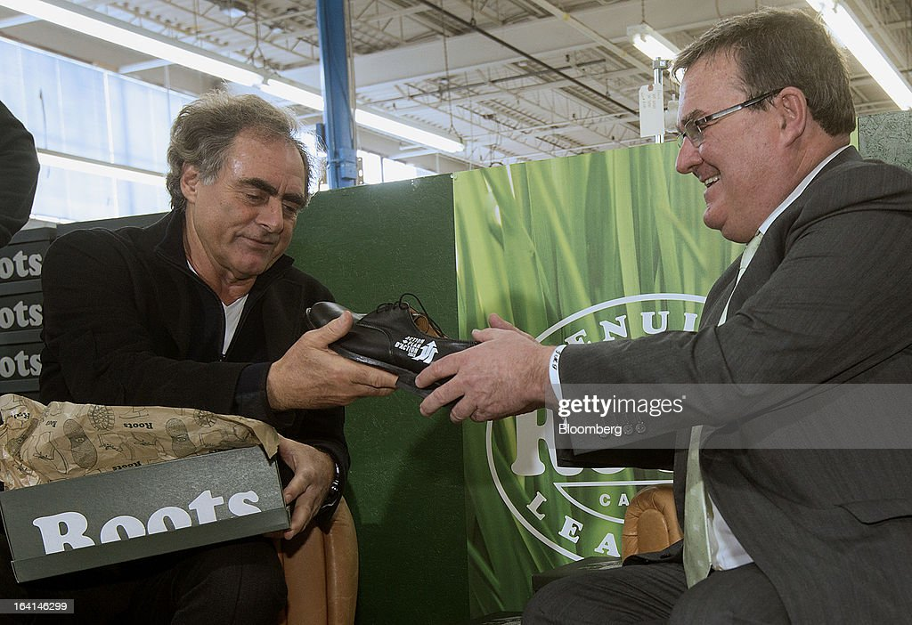 Michael Budman, founder of Roots Ltd., left, hands <a gi-track='captionPersonalityLinkClicked' href=/galleries/search?phrase=Jim+Flaherty+-+Politician&family=editorial&specificpeople=12721315 ng-click='$event.stopPropagation()'>Jim Flaherty</a>, Canada's finance minister, center, a pair of shoes to try on for purchasing, a pre-budget tradition, at the Roots manufacturing facility in Toronto, Ontario, Canada, on Wednesday, March 20, 2013. Flaherty said his budget tomorrow will seek to balance the need for sound government finances with growth-promoting steps, including measures to help the nation's manufacturers. Photographer: Norm Betts/Bloomberg via Getty Images