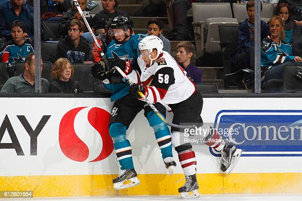 Michael Bunting of the Arizona Coyotes checks Tim Heed of the San Jose Sharks into the boards at SAP Center on September 30 2016 in San Jose...