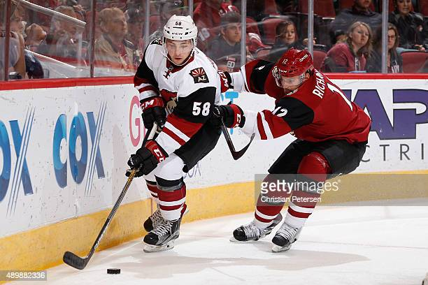 Michael Bunting of the White team skates with the puck ahead of Brad Richardson of the Red team during the first period of the Arizona Coyotes...