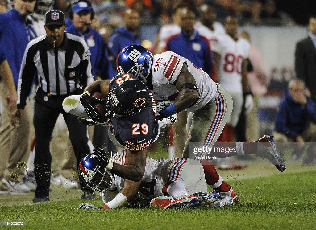 Michael Bush of the Chicago Bears is tackled by Jon Beason of the New York Giants during the second half on October 10 2013 at Soldier Field in...