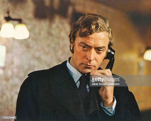 Michael Caine British actor wearing a black raincoat and holding a black telephone receiver in a publicity still issued for the film 'Get Carter'...