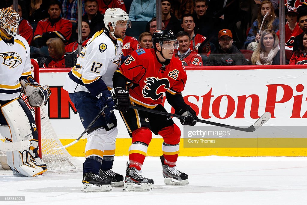 Michael Cammalleri #13 of the Calgary Flames skates against Mike Fisher #12 of the Nashville Predators on March 15, 2013 at the Scotiabank Saddledome in Calgary, Alberta, Canada.