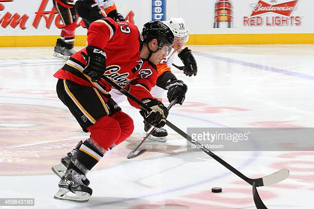 Michael Cammalleri of the Calgary Flames skates the puck against Michael Raffl of the Philadelphia Flyers at Scotiabank Saddledome on December 31...