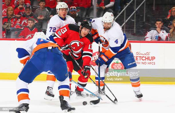 Michael Cammalleri of the New Jersey Devils and Dennis Seidenberg of the New York Islanders battle for a loose puck during the game at Prudential...