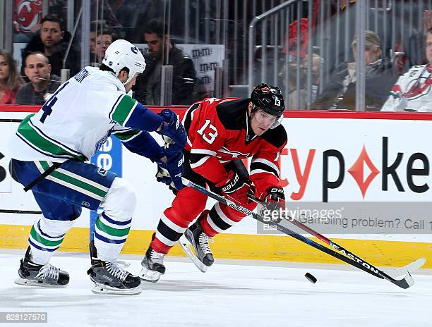 Michael Cammalleri of the New Jersey Devils takes the puck as Erik Gudbranson of the Vancouver Canucks defends on December 6 2016 at Prudential...