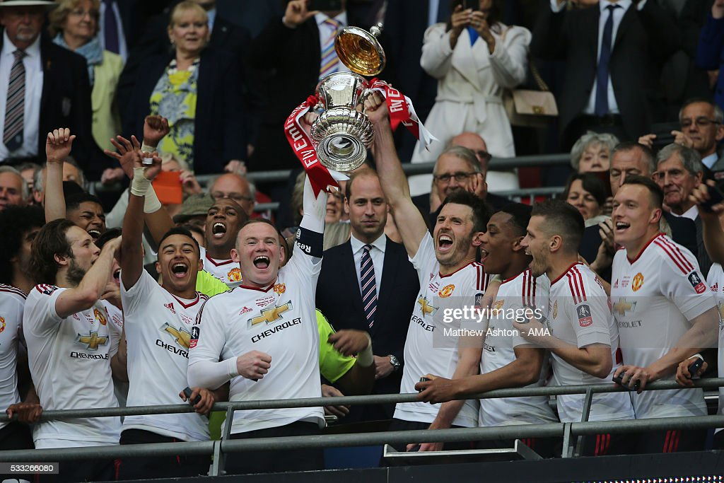 Michael Carrick and Wayne Rooney of Manchester United lift the trophy following their 12 victory at the end of extra time during The Emirates FA Cup...