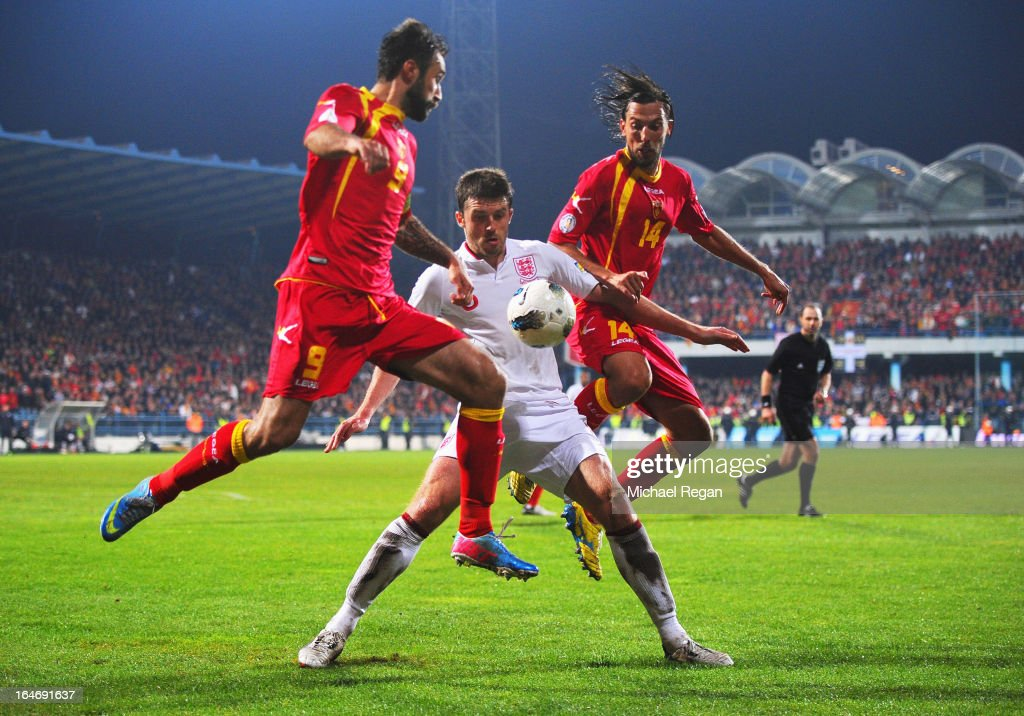<a gi-track='captionPersonalityLinkClicked' href=/galleries/search?phrase=Michael+Carrick&family=editorial&specificpeople=214599 ng-click='$event.stopPropagation()'>Michael Carrick</a> of England (C) battles with <a gi-track='captionPersonalityLinkClicked' href=/galleries/search?phrase=Mirko+Vucinic&family=editorial&specificpeople=860475 ng-click='$event.stopPropagation()'>Mirko Vucinic</a> (9) and Dejan Damjanovic (14) of Montenegro during the FIFA 2014 World Cup Qualifier Group H match between Montenegro and England at City Stadium on March 26, 2013 in Podgorica, Montenegro.