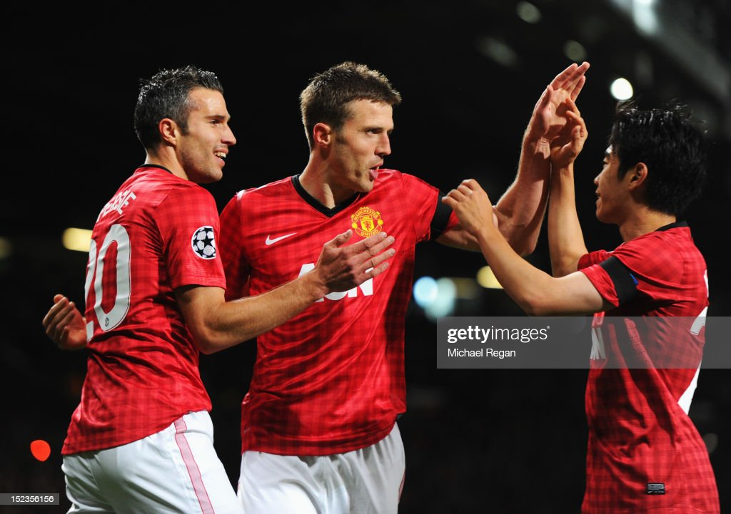 <a gi-track='captionPersonalityLinkClicked' href=/galleries/search?phrase=Michael+Carrick&family=editorial&specificpeople=214599 ng-click='$event.stopPropagation()'>Michael Carrick</a> of Manchester United (C) celebrates with Robin van Persie (L) and <a gi-track='captionPersonalityLinkClicked' href=/galleries/search?phrase=Shinji+Kagawa&family=editorial&specificpeople=4314029 ng-click='$event.stopPropagation()'>Shinji Kagawa</a> (R) as he scores their first goal during the UEFA Champions League Group H match between Manchester United and Galatasaray at Old Trafford on September 19, 2012 in Manchester, England.