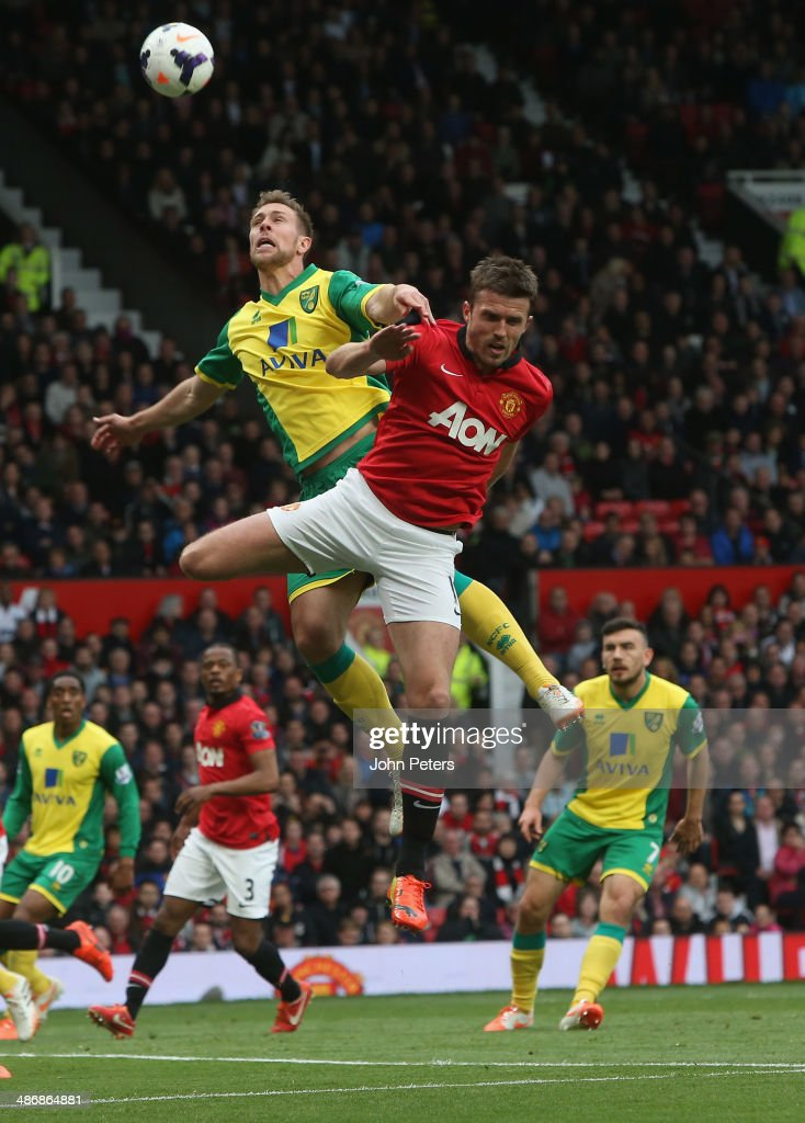 Michael Carrick of Manchester United ina ction with Steven Whittaker during the Barclays Premier League match between Manchester United and Norwich at Old Trafford on April 26, 2014 in Manchester, England.