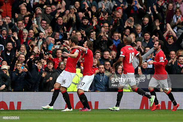 Michael Carrick of Manchester United is congratulated by teammates after scoring his team's second goal with a header during the Barclays Premier...