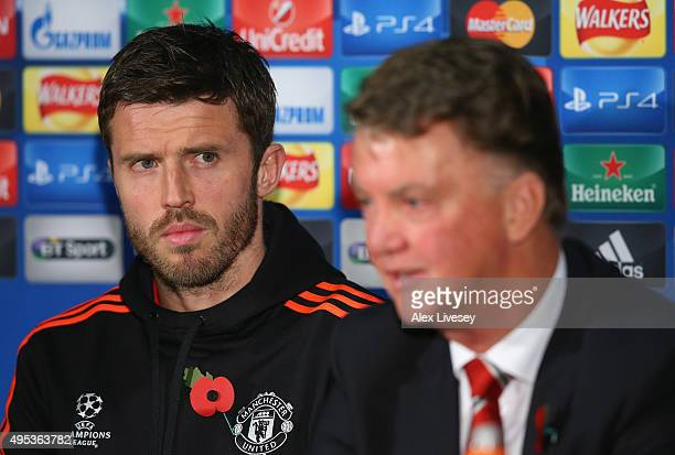 Michael Carrick of Manchester United looks on as Louis van Gaal the manager of Manchester United faces the media during a press conference on the eve...