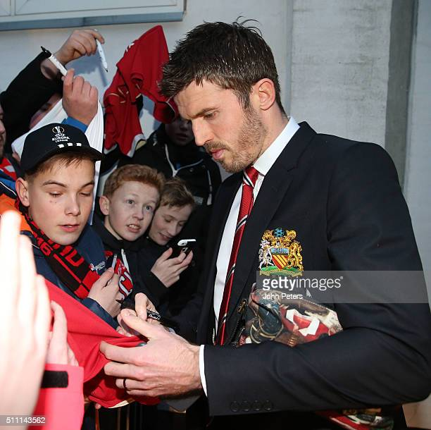 Michael Carrick of Manchester United signs autographs for fans as he leaves the team hotel ahead of their UEFA Europe League match against FC...