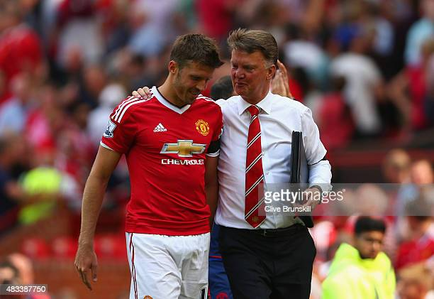 Michael Carrick of Manchester United walks with Louis van Gaal Manager of Manchester United after the Barclays Premier League match between...