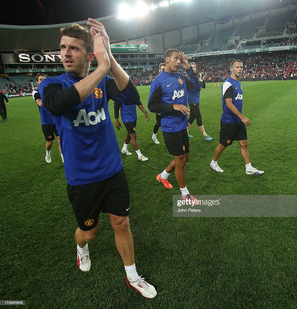 Michael Carrick, Rio Ferdinand and Ryan Giggs of Manchester United applaud the fans after a first team training session as part of their pre-season tour of Bangkok, Australia, China, Japan and Hong Kong on July 19, 2013 in Sydney, Australia.