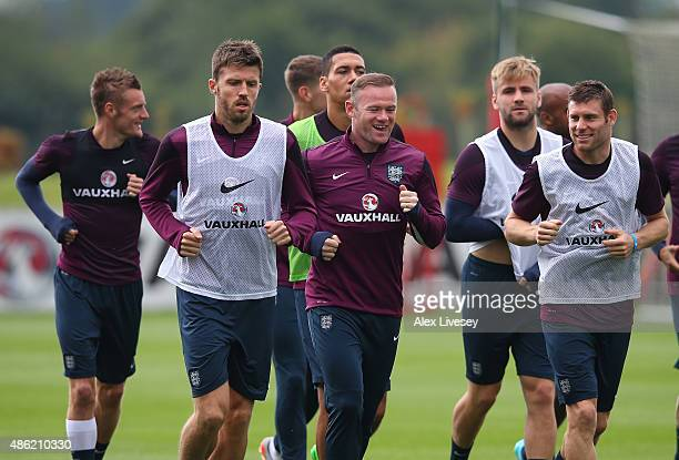 Michael Carrick Wayne Rooney and James Milner of England warm up during a England training session at St Georges Park on September 2 2015 in...