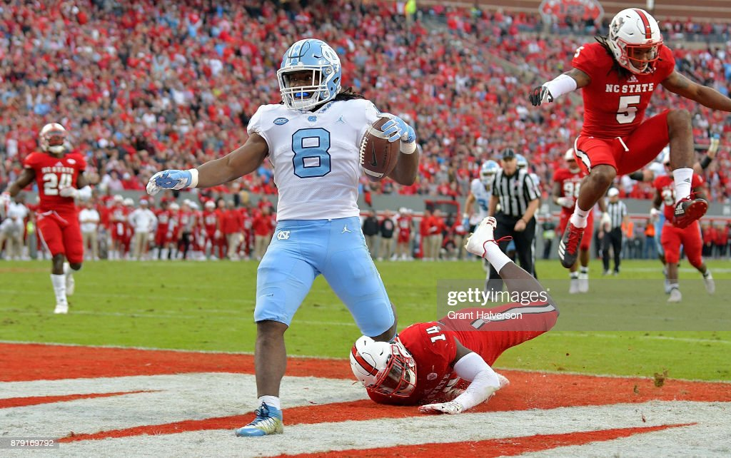 Michael Carter #8 of the North Carolina Tar Heels beats Dexter Wright #14 of the North Carolina State Wolfpack for a touchdown during their game at Carter Finley Stadium on November 25, 2017 in Raleigh, North Carolina.