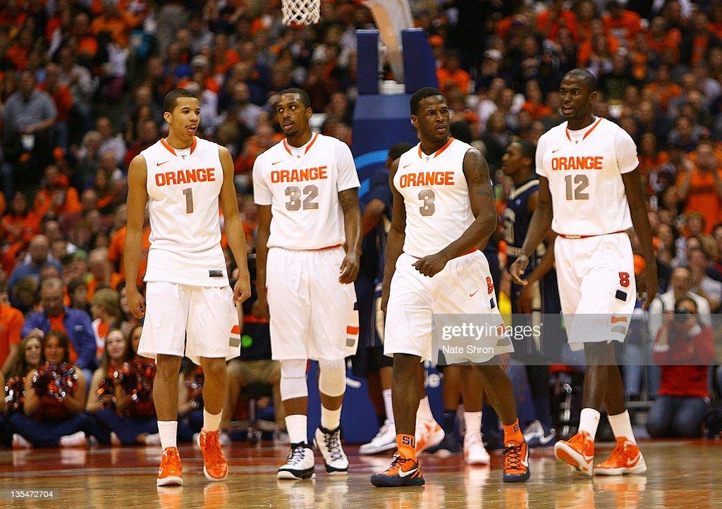 Michael CarterWilliams Kris Joseph Dion Waiters and Baye Keita of the Syracuse Orange walk on the court during the game against the George Washington...
