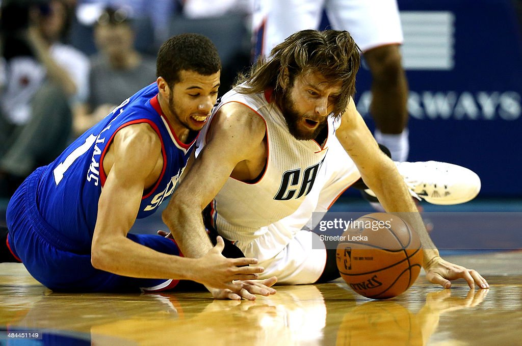 Michael Carter-Williams #1 of the Philadelphia 76ers and Josh McRoberts #11 of the Charlotte Bobcats dive for a loose ball during their game at Time Warner Cable Arena on April 12, 2014 in Charlotte, North Carolina.