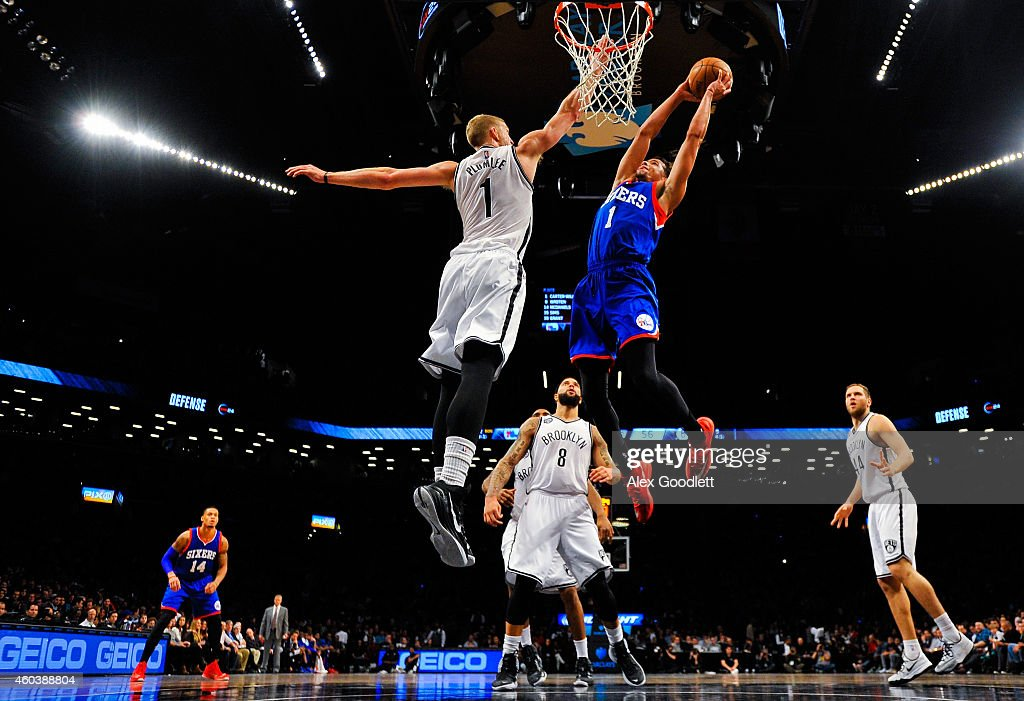 Michael Carter-Williams #1 of the Philadelphia 76ers dunks over Mason Plumlee #1 of the Brooklyn Nets in the second half at the Barclays Center on December 12, 2014 in the Brooklyn borough of New York City.