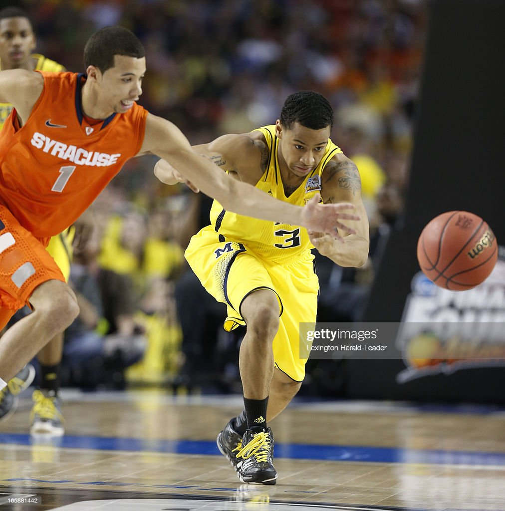 Michael Carter-Williams (1) of the Syracuse Orange and Trey Burke (3) of the Michigan Wolverines chase a loose ball in first-half action in an NCAA Final Four semifinal at the Georgia Dome in Atlanta, Georgia, Saturday, April 6, 2013.