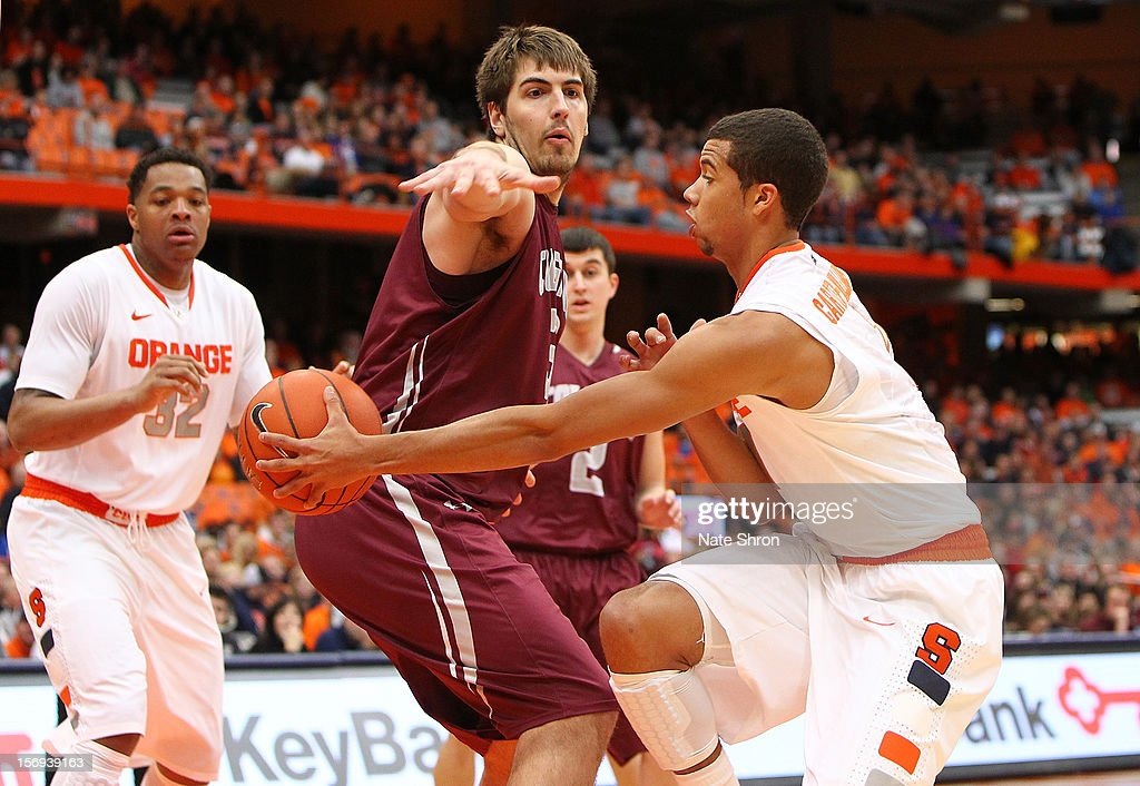 Michael Carter-Williams #1 of the Syracuse Orange attempts to pass the ball to teammate DaJuan Coleman #32 as he is guarded by John Brandenburg #3 of the Colgate Raiders as teammate Mitch Rolls #2 looks on during the game at the Carrier Dome on November 25, 2012 in Syracuse, New York.