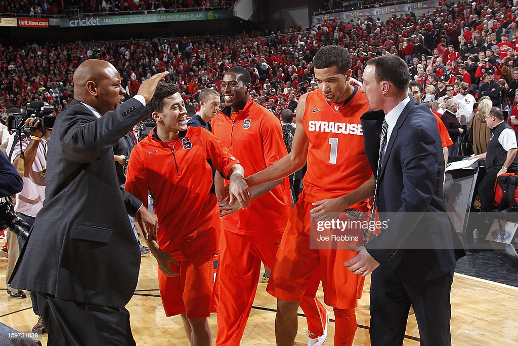 Michael Carter-Williams #1 of the Syracuse Orange celebrates with coaches and teammates after the game against the Louisville Cardinals at KFC Yum! Center on January 19, 2013 in Louisville, Kentucky. Syracuse defeated Louisville 70-68.
