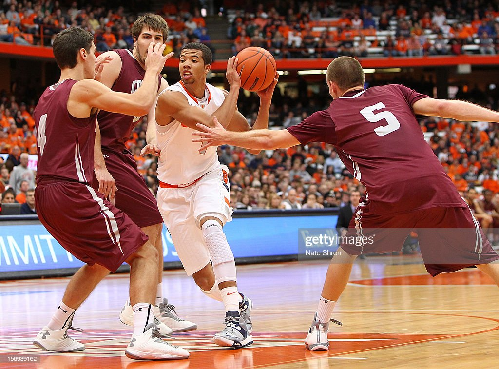 Michael Carter-Williams #1 of the Syracuse Orange drives to the basket against Pat Moore #5, Luke Roh #4 and John Brandenburg #3 of the Colgate Raiders during the game at the Carrier Dome on November 25, 2012 in Syracuse, New York.