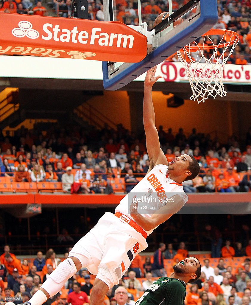 Michael Carter-Williams #1 of the Syracuse Orange falls backwards as he puts the ball up to the basket against Kenneth Ortiz #15 of the Wagner Seahawks during the game at the Carrier Dome on November 18, 2012 in Syracuse, New York.