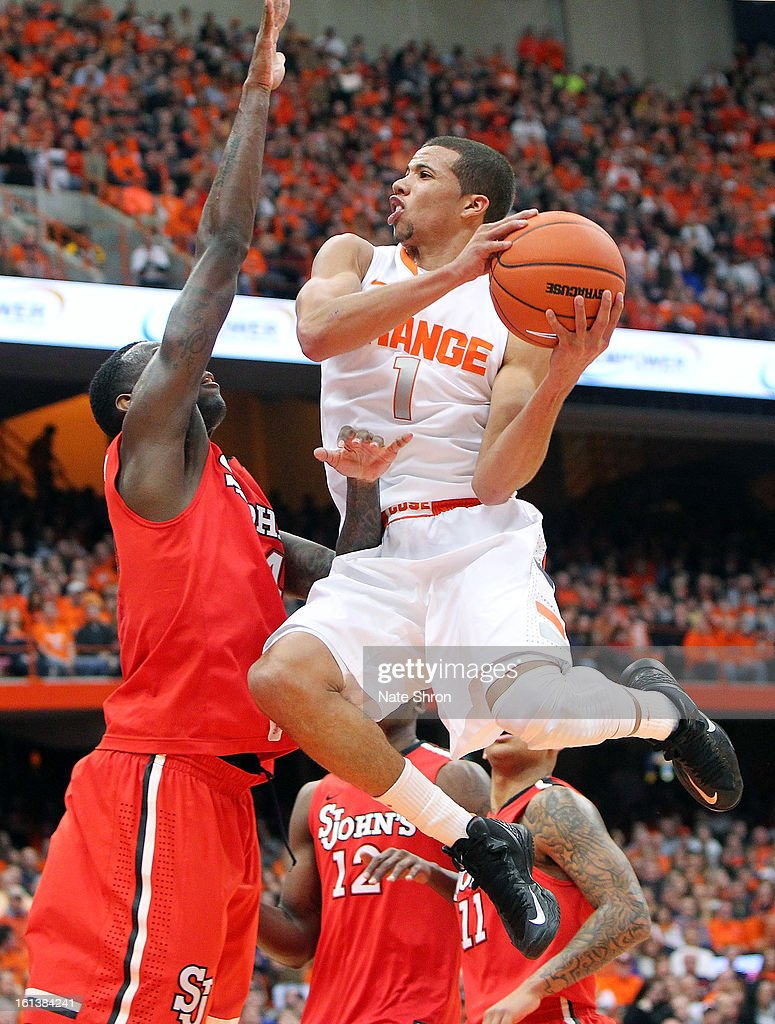 Michael Carter-Williams #1 of the Syracuse Orange puts the ball up to the basket against Jakarr Sampson #14 of the St. John's Red Storm during the game at the Carrier Dome on February 10, 2013 in Syracuse, New York.