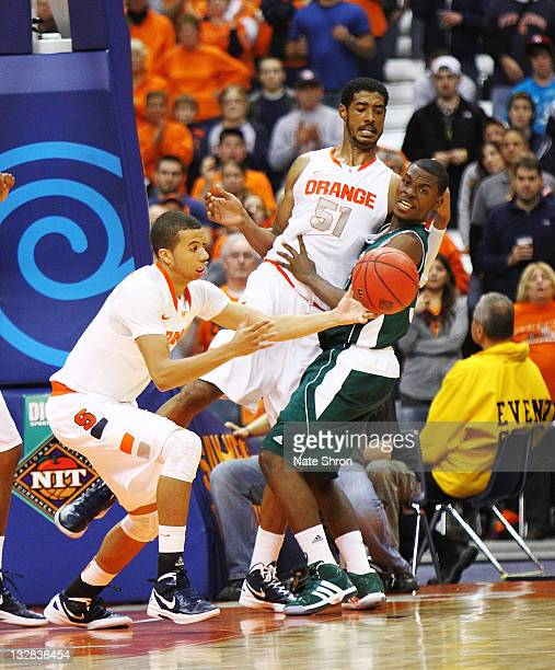 Michael CarterWilliams of the Syracuse Orange reaches for the rebound from teammate Fab Melo as he is blocked by Donovan Kates of the Manhattan...