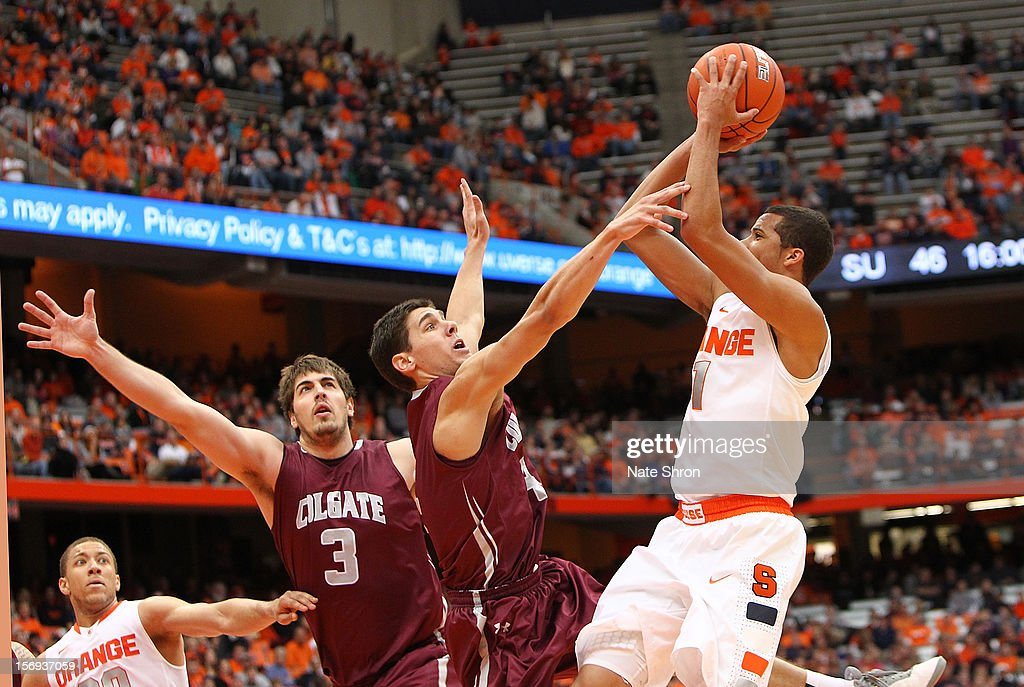 Michael Carter-Williams #1 of the Syracuse Orange shoots the ball as teammate Brandon Triche #20 looks on against John Brandenburg #3 and Luke Roh #4 of the Colgate Raiders during the game at the Carrier Dome on November 25, 2012 in Syracuse, New York.