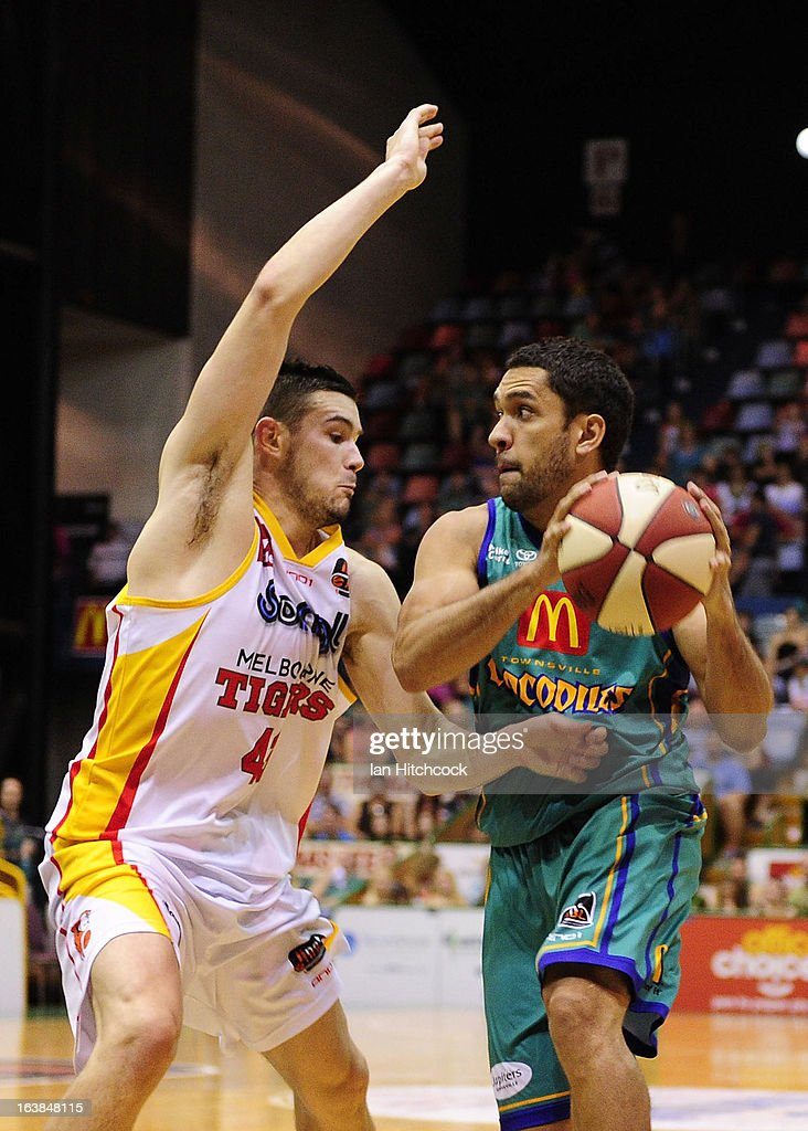 Michael Cedar of the Crocodiles looks to pass the ball past Chris Goulding of the Tigers during the round 23 NBL match between the Townsville Crocodiles and the Melbourne Tigers at Townsville Entertainment Centre on March 17, 2013 in Townsville, Australia.