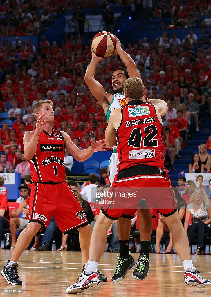 Michael Cedar of the Crocodiles passes the ball against Rhys Carter and Shawn Redhage of the Wildcats during the round 19 NBL match between the Perth Wildcats and the Townsville Crocodiles at Perth Arena on February 15, 2013 in Perth, Australia.