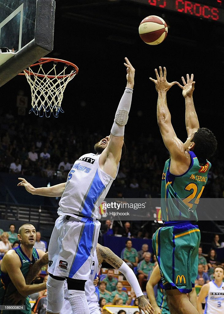 Michael Cedar of the Crocodilescontests the ball with Will Hudson of the Breakers during the round 14 NBL match between the Townsville Crocodiles and the New Zealand Breakers at Townsville Entertainment Centre on January 11, 2013 in Townsville, Australia.