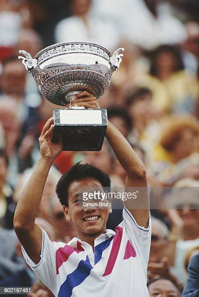 Michael Chang of the United States holds aloft the trophy after winning the Men's Singles Final against Stefan Edberg at the French Open Tennis...