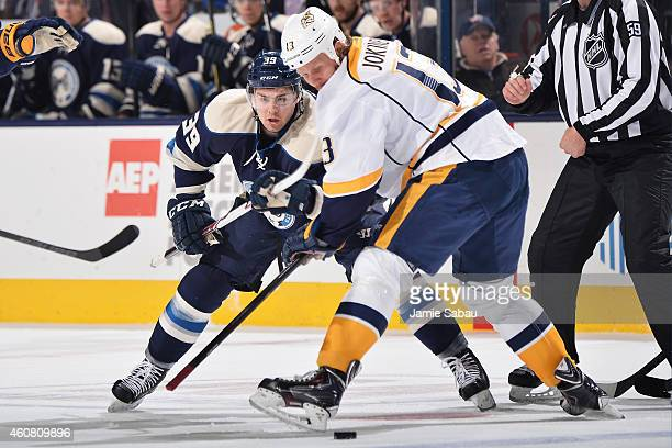 Michael Chaput of the Columbus Blue Jackets and Olli Jokinen of the Nashville Predators battle for a loose puck during the first period on December...