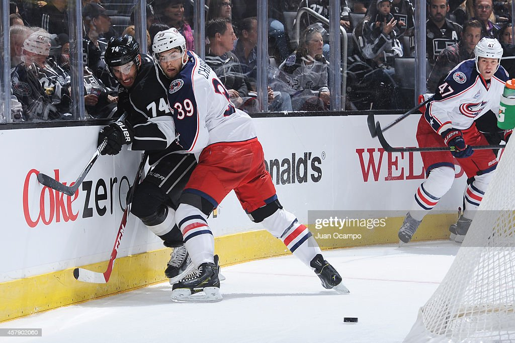 Michael Chaput #39 of the Columbus Blue Jackets checks Dwight King #74 of the Los Angeles Kings into the boards at STAPLES Center on October 26, 2014 in Los Angeles, California.