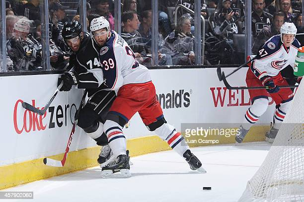 Michael Chaput of the Columbus Blue Jackets checks Dwight King of the Los Angeles Kings into the boards at STAPLES Center on October 26 2014 in Los...