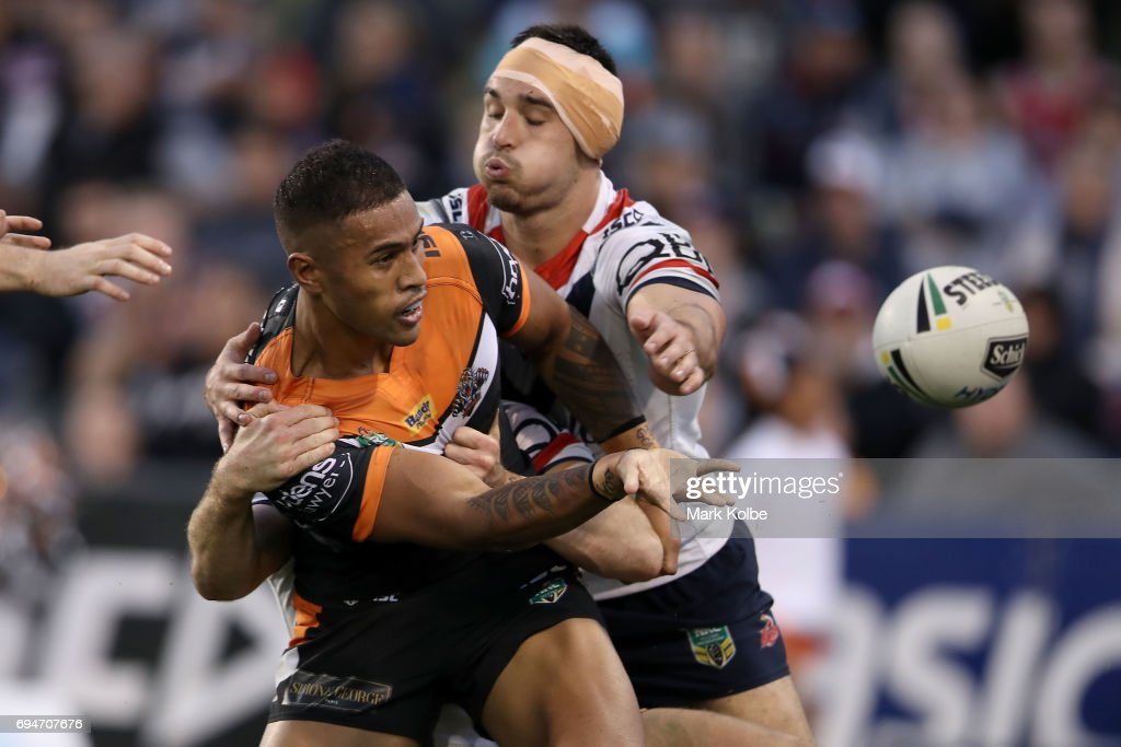 Michael Chee-Kam of the Tigers passes as he is tackled by Ryan Matterson of the Roosters during the round 14 NRL match between between the Wests Tigers and the Sydney Roosters at Campbelltown Sports Stadium on June 11, 2017 in Sydney, Australia.