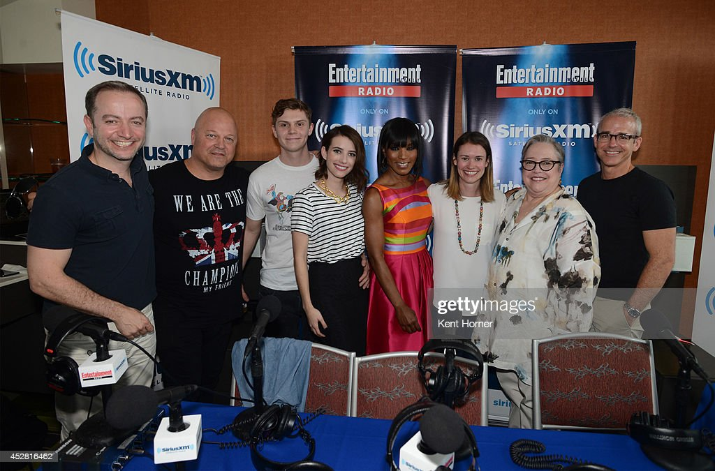 Michael Chiklis Evan Peters Emma Roberts Angela Bassett and Kathy Bates pose with radio hosts Mario Correa and Jess Cagle after being interviewed on...