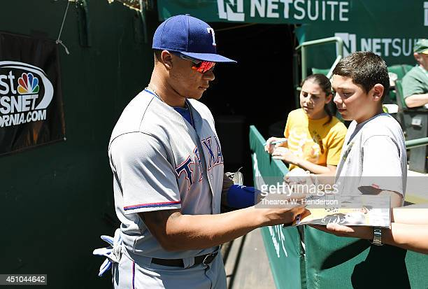 Michael Choice of the Texas Rangers signs autographs for fans prior to the start of his game against the Oakland Athletics at Oco Coliseum on June 18...