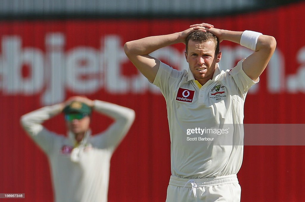 Michael Clarke and Peter Siddle of Australia look on after Ed Cowan dropped a catch off Siddles bowling during day five of the Second Test Match between Australia and South Africa at Adelaide Oval on November 26, 2012 in Adelaide, Australia.