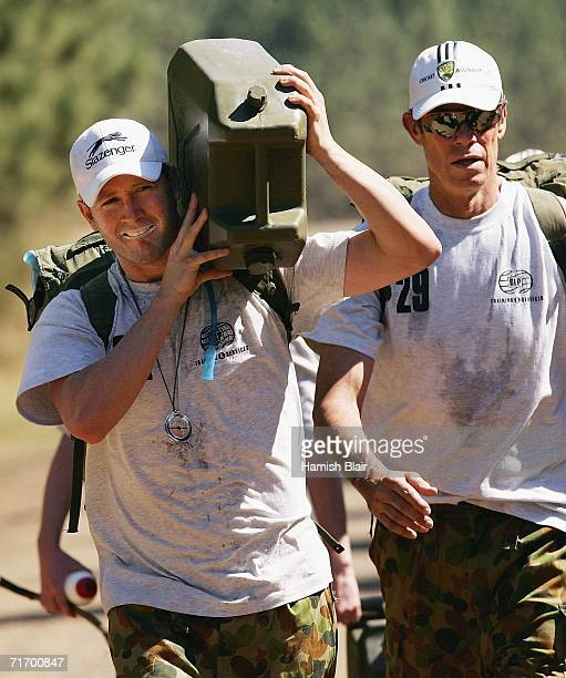 Michael Clarke of Australia carries a jerry can of water as coach John Buchanan looks on during an outback boot camp training session in the Beerwah...