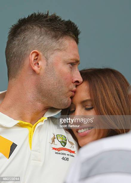 Michael Clarke of Australia kisses his wife Kyly Clarke as he waits during a rain delay during day two of the First Test match between Australia and...