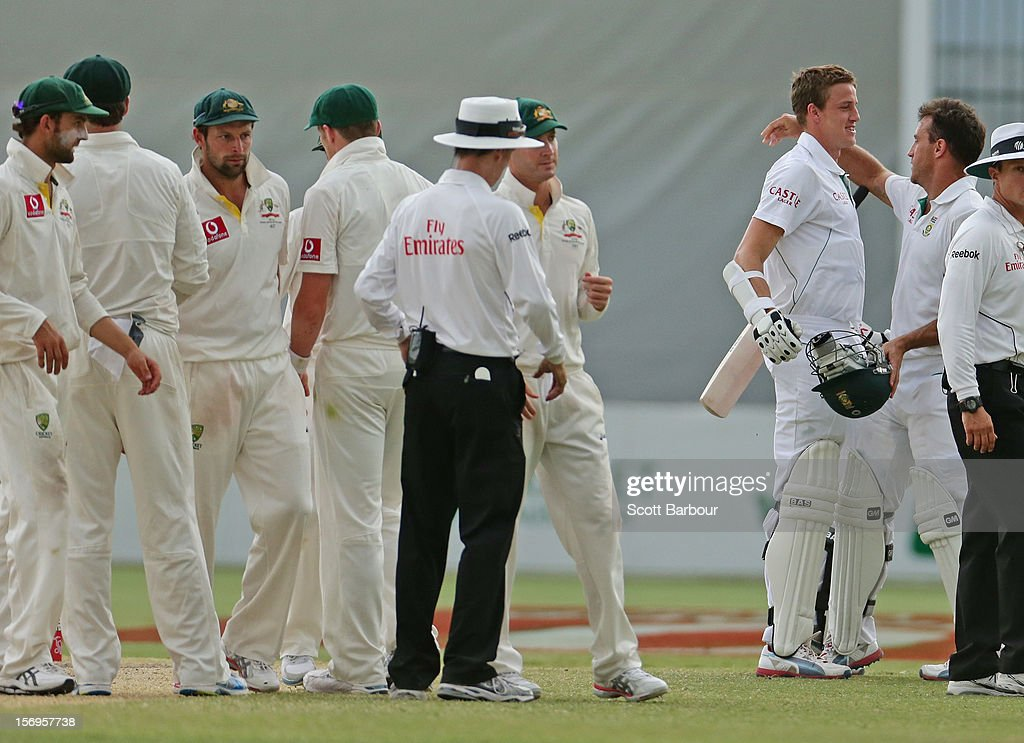 Michael Clarke of Australia looks on as Faf du Plessis and Morne Morkel of South Africa embrace at the conclusion of day five of the Second Test Match between Australia and South Africa at Adelaide Oval on November 26, 2012 in Adelaide, Australia.
