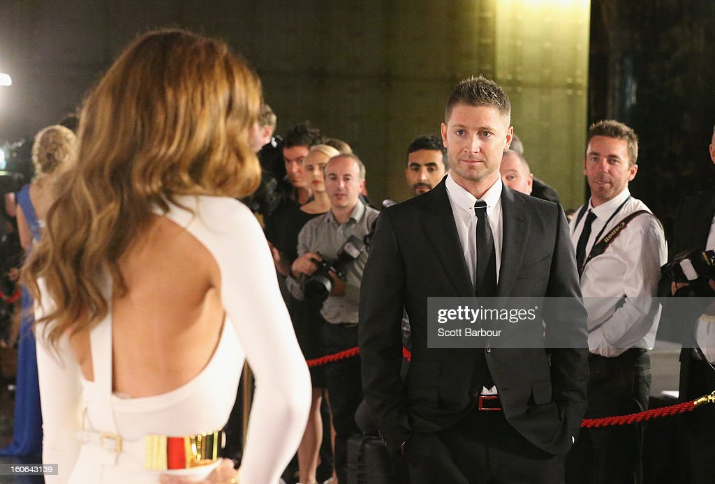 Michael Clarke of Australia looks on as his wife Kyly Clarke (L) poses for photographers as they arrive at the 2013 Allan Border Medal awards ceremony at Crown Palladium on February 4, 2013 in Melbourne, Australia.