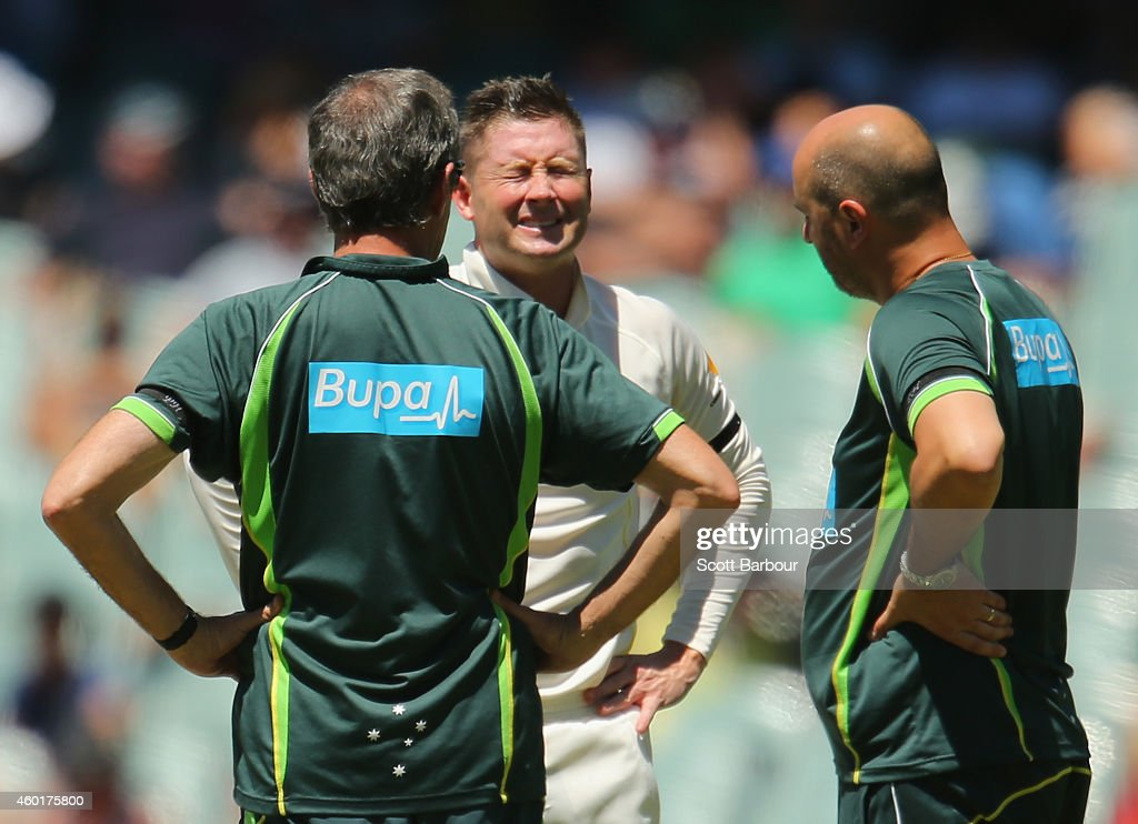 <a gi-track='captionPersonalityLinkClicked' href=/galleries/search?phrase=Michael+Clarke+-+Cricketspeler&family=editorial&specificpeople=175853 ng-click='$event.stopPropagation()'>Michael Clarke</a> of Australia reacts as he injures his back as he is tended to by <a gi-track='captionPersonalityLinkClicked' href=/galleries/search?phrase=Peter+Brukner&family=editorial&specificpeople=5370816 ng-click='$event.stopPropagation()'>Peter Brukner</a> (L), Australian Team Doctor and Alex Kountouris, Australian Team Physiotherapist during day one of the First Test match between Australia and India at Adelaide Oval on December 9, 2014 in Adelaide, Australia.