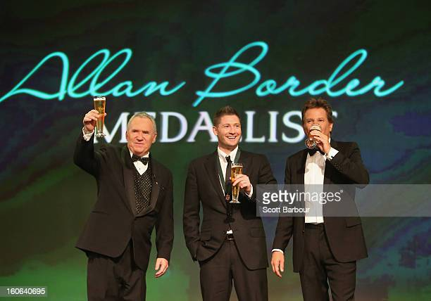 Michael Clarke of Australia shares a toast with Allan Border and Mark Nicholas on stage after winning the Allan Border Medal during the 2013 Allan...