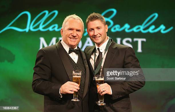 Michael Clarke of Australia shares a toast with Allan Border on stage after winning the Allan Border Medal during the 2013 Allan Border Medal awards...