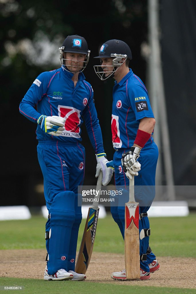 Michael Clarke of the Kowloon Cantons (L) confers with Australian compatriot and teammate Ryan Campbell as they play against Hung Hom JD Jaguars during the Hong Kong T20 Blitz cricket tournament in Hong Kong on May 28, 2016. Former Australia captain Michael Clarke on May 27 said his body felt 15 years younger after a spell away from cricket as he prepared for a comeback at the Hong Kong T20 Blitz. / AFP / TENGKU